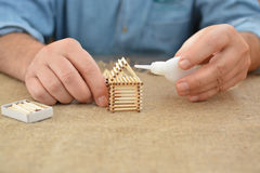 The man is engaged in manual work glue house with matches. Handmade. Blurring background. Free place. Needlework. Hobby. The man is engaged in manual work glue Royalty Free Stock Photo