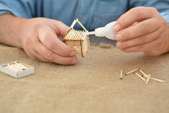 The man is engaged in manual work glue house with matches. Handmade. Blurring background. Free place. Needlework. Hobby. The man is engaged in manual work glue Stock Image