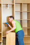 The man is engaged in repair and furniture Stock Photos
