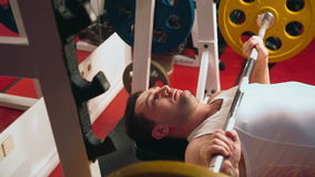 The man is engaged in a sports hall. Man lie down on the fitness machine and raises the bar in the gym stock video