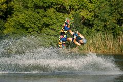 A man engaged in wakeboard on the lake performs jumps stock photography
