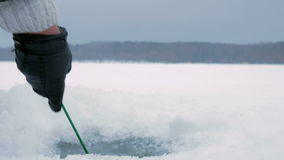 The man is engaged in winter fishing on a frozen lake. Clears the hole on the ice crust. stock video footage