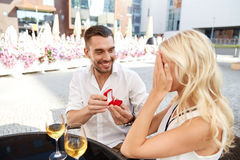 Man with engagement ring making proposal to woman. Love, anniversary, surprise, people and holidays concept - happy men with engagement ring making proposal to Royalty Free Stock Images