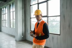 Man engineer hold tablet wearing hardhat and veils. Working in the new hall building stock photos