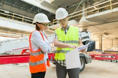 Man engineer and woman architect at a construction site. Building, development, teamwork and people concept. Man engineer and women architect at a construction stock images