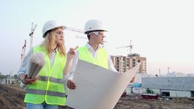 Man engineer and woman architect at a construction site. Building, development, teamwork and people concept. Man. Engineer and women architect at a construction stock video footage