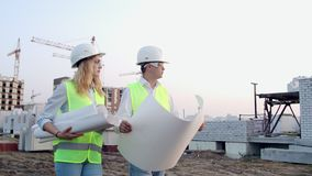 Man engineer and woman architect at a construction site. Building, development, teamwork and people concept. Man stock video footage