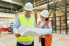 Man engineer and woman architect at a construction site. Building, development, teamwork and people concept. Man engineer and women architect at a construction stock image