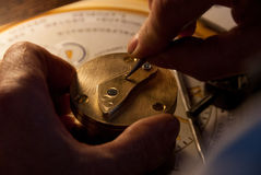 Man engraving a letter on brass. Close-up on the hands of a man engraving a letter on brass with a warm orange light on a blurred background Royalty Free Stock Images