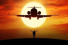 Man enjoy freedom on the hill under flying plane Stock Image