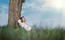 Man enjoy in music. Sideways - profile of young man listen music - enjoy - repose in grass. Guy leaning against a tree relaxing - resting. Outdoors - outside Stock Photography