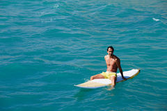 Man enjoy vacation at sea. Shot of a handsome young man enjoying a surf in clear blue water, male surfer in the ocean water with surf board, man surfing at the royalty free stock image