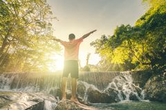Happy man enjoying amazing tropical waterfall raised hands Travel Lifestyle and success concept vacations. A man enjoying amazing tropical waterfall raised hands royalty free stock image
