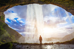 Man enjoying amazing view of nature. Incredible waterfall in Iceland, silhouette of man enjoying amazing view of nature