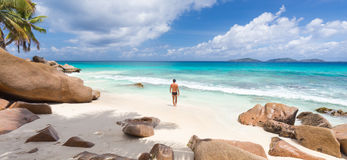 Man enjoying Anse Patates picture perfect beach on La Digue Island, Seychelles. Stock Photos