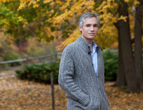 Man Enjoying Autumn. A handsome man with gray hair poses in front of a beautiful colorful fall / autumn background Stock Photography