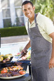 Man Enjoying A Barbequed Meal In The Garden. Smiling royalty free stock image
