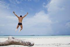 Man enjoying on the beach. Man jumping from a trunk enjoying on the beach Stock Photos