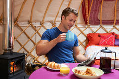 Man Enjoying Breakfast Whilst Camping In Traditional Yurt Stock Photos