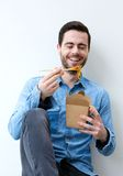Man enjoying chinese food with chopsticks Royalty Free Stock Images