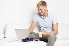 Man enjoying a cup of coffee while working on computer. Royalty Free Stock Photography