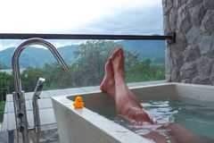 A man is enjoying a dip in the hot tub with mountain front.  royalty free stock image