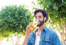 Man enjoying a drink of beer in summer at outdoor bar Royalty Free Stock Image