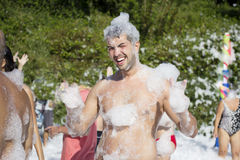 Man  enjoying  a foam party on the beach Stock Photos