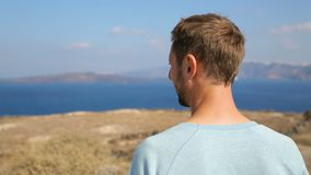 Man enjoying freedom of his being looking at magic landscape of Santorini island. Stock footage stock footage