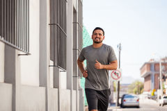 Man enjoying going for a run outdoors. Portrait of a good looking young man enjoying his run around the city and smiling Stock Photo