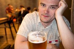 Man enjoying his beer. Whilst waiting for a plane stock photo
