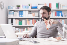 Man enjoying his lunch break. Smiling man having a lunch break at office, he is eating a slice of pizza and social networking with a laptop stock photography