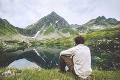 Man enjoying landscape traveling alone adventure vacations. Solitude lifestyle outdoor silence lake and mountains reflection landscape royalty free stock photo