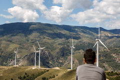 Man enjoying a landscape with windmills in the background Stock Photos