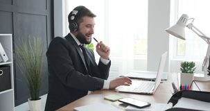 Man enjoying while listening and singing music at office. Businessman listening and singing song while working on laptop at office desk stock footage