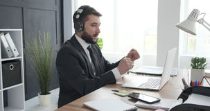 Man enjoying while listening and singing music at office stock video footage