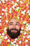 Man enjoying lying in sweet stuff. Bearded smiling man enjoying lying in big pile of jellies, candies and marshmallows Royalty Free Stock Photography