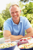 Man Enjoying Meal In Garden Stock Image
