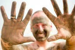 Man enjoying mud from Dead Sea, Israel Stock Images