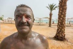 Man enjoying mud from Dead Sea, Israel Royalty Free Stock Image