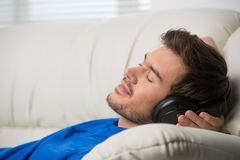 Man enjoying music lying on couch. Royalty Free Stock Image