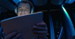 Man enjoying music with pad at sky deck at night stock footage