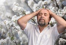 Man enjoying nature in the flowered garden Stock Images