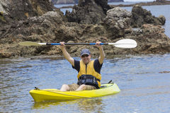 Man enjoying an ocean kayaking trip Stock Images