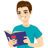 Man Enjoying Reading. Young brown haired man happy enjoying reading big thick book Royalty Free Stock Images