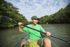Man enjoying river kayaking through mangrove jungl stock photo