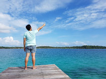 Man enjoying sea landscape while standing on beach wooden pier with raised hand against sky background with copy space area for yo Stock Images