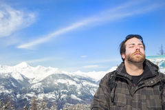 Man enjoying the sunshine and tranquility. In a cold snowy mountainous terrain with his head tilted back and eyes closed in meditation against a hazy blue sky royalty free stock photography