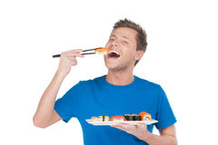 Man enjoying sushi. Handsome young man holding a plate of sushi and eating while standing isolated on white Stock Images