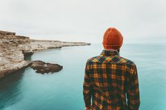 Man enjoying view of cold sea Travel Fashion Lifestyle. Orange hat and cozy shirt clothing harmony with nature authentic style concept Royalty Free Stock Image